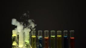 Multicolor ciecze w próbnych tubkach emituje dym w ciemnym laboratorium, narkotyk zbiory