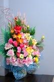Multicolor de flores artificiales en la tabla adorne el cuarto Imágenes de archivo libres de regalías