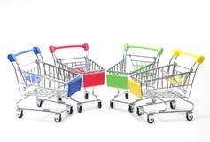 Multicolor del mini carro de la compra en el fondo blanco imagen de archivo