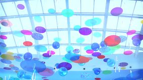 Multicolor discs swinging and rotating under glass roof stock video