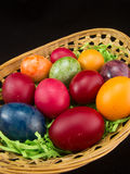 Multicolor easter eggs in basket. On black Royalty Free Stock Photo
