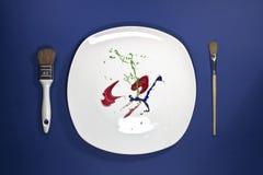 Maluje na talerzu z farb muśnięciami na stronie ilustracji
