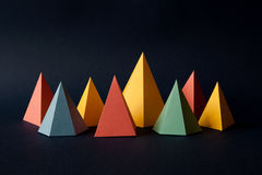 Multicolor geometric abstract background. Bright prism pyramid triangle shape figures on dark paper. Violet yellow blue Royalty Free Stock Photo