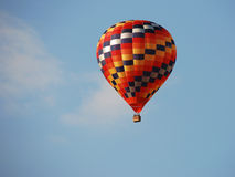 Multicolor hot air balloon. Over a blue sky Stock Images