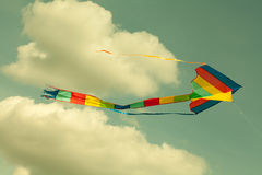 Multicolor kite flying in the cloudy sky. Royalty Free Stock Images