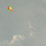 Multicolor kites flying in the cloudy sky. Retro style. Royalty Free Stock Image