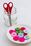 Multicolor knappar på den vita plattan Royaltyfri Fotografi