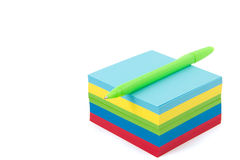Multicolor memo pad with pen on it. Multicolor memo pad with green ballpoint pen on it isolated Stock Images
