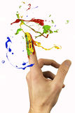 Multicolor paint circulating around forefinger. Multicolor paint circulating around painted forefinger Royalty Free Stock Photo