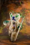 Multicolor paintbrush in hand of a magic teddy bear Stock Photos