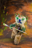 Multicolor paintbrush in hand of a wizard teddy bear Royalty Free Stock Image