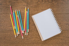 Multicolor pencils and blank notebook on wooden background Royalty Free Stock Images