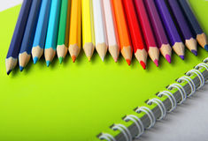 Multicolor pencils on green notebook Stock Images