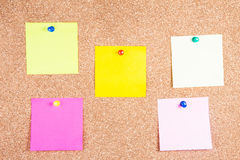 Multicolor reminder sticky notes on cork board Royalty Free Stock Images