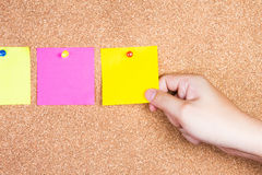 Multicolor reminder sticky notes on cork board with hand holding Royalty Free Stock Image