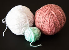 Multicolor rolls of worsted yarn over black background Royalty Free Stock Image