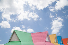 Multicolor roof on blue sky background . Stock Photos