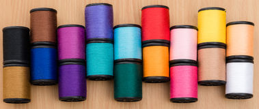 Multicolor sewing threads background. Wooden background. Bobbins of multi color thread Royalty Free Stock Photo