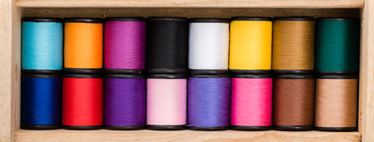 Multicolor sewing threads background. Wooden background. Colorful threads on wooden Royalty Free Stock Images