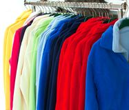 Multicolor sport shirts hanging in store. Colourful Textile sport shirts hanging in row at store Royalty Free Stock Photos