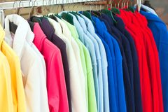 Multicolor sport shirts hanging in store. Colourful Textile sport shirts hanging in row at store Stock Photography