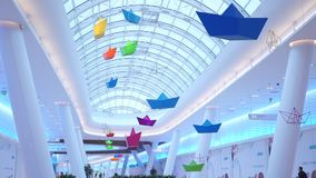Multicolor stylized paper boats swinging and rotating under glass ceiling stock video