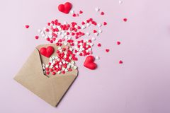 Multicolor sweets sugar candy hearts fly out of craft paper postal envelope. Happy Valentine`s dayconcept. Royalty Free Stock Images