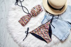 Multicolor swimsuit, straw hat and denim shorts. White fur on th. E background, top view Royalty Free Stock Photography