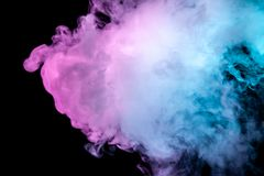 Multicolor, thick smoke, illuminated by colored in blue, purple and pink light against a dark black isolated background, welded royalty free stock photos