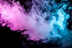 Multicolor, thick smoke, illuminated by colored in blue, purple and pink light against a dark black isolated background, welded stock photography