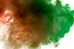 Multicolor, thick smoke, illuminated by colored in green and red light against a white isolated background, welded with clubs and royalty free stock photo