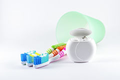 Multicolor toothbrushes and dental floss on white background. Daily oral hygiene - toothbrushes and dental floss  on white background Stock Photos