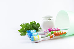 Multicolor toothbrushes and dental floss on white background. Daily oral hygiene - toothbrushes and dental floss isolated on white background Stock Photos