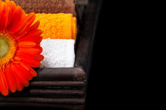 Multicolor towels and orange gerbera daisy Royalty Free Stock Photography