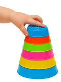 Multicolor tower of cups. And child's hand Royalty Free Stock Image