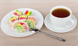 Multicolor Turkish delight in plate and cup of hot tea Royalty Free Stock Images