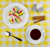 Multicolor Turkish delight in plate, cup of tea and cinnamon Royalty Free Stock Photography