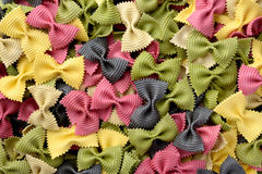 Multicolor uncooked farfalle pasta background Stock Images
