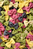 Multicolor uncooked farfalle pasta background Stock Photo