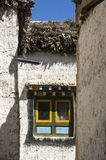 Multicolor window in the streets of Lo Manthang, Mustang. Front details of a traditional tibetan house in Mustang. Multicolor painting, wooden stock on the roof Stock Photography
