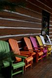 Multicolored adirondack chairs outside log cabin. Multicolored adirondack chairs sitting in a row outside a log cabin wall - rich colors Royalty Free Stock Images