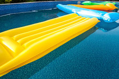 Multicolored air mattresses floating on the calm surface of a smaller pool Stock Images