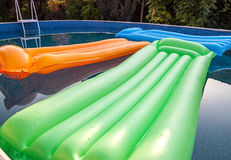 Multicolored air mattresses floating on the calm surface of a smaller pool Royalty Free Stock Photo