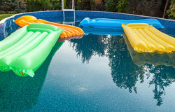 Multicolored air mattresses floating on the calm surface of a smaller pool Stock Photography