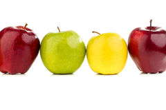 Multicolored apples in a row on a white table. On a white background Royalty Free Stock Photography