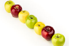 Multicolored apples in a row on a white table. On a white background Stock Photo
