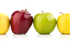 Multicolored apples in a row on a white table. On a white background Royalty Free Stock Images