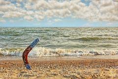 Multicolored Australian Boomerang on sandy beach against of sea Stock Photos