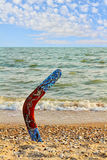 Multicolored Australian Boomerang on sandy beach near sea surf a Stock Images