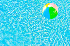 Multicolored ball and turquoise water with ripples Stock Photography